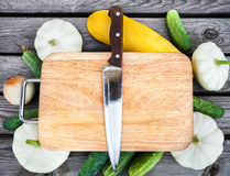 Cutting board, knife, fresh vegetables on wooden table.  Top vie Royalty Free Stock Images