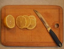On the cutting Board is a knife and a lemon, cut into circles