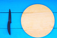 Cutting board and knife on wooden kitchen table Royalty Free Stock Photos