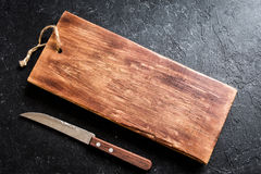 Cutting board and knive. Rustic wooden cutting board and knive on black stone background close up - rustic empty copy space for text, design element Stock Photos