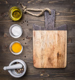 Cutting board with oil, salt and pepper with mortar wooden rustic background top view close up Stock Image