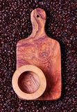 Cutting board of olive wood on the background of coffee beans Royalty Free Stock Images