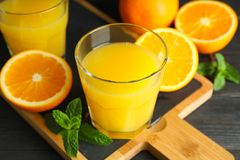 Cutting board with orange juice, mint and oranges on wooden table against black background, closeup. Fresh drinks and fruits royalty free stock image