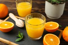 Cutting board, orange juice, wooden juicer, mint, orange, tubule and succulent plant on wooden table, closeup. Fresh natural drink and fruits stock photography