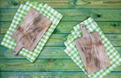 Cutting board over green checkered tablecloth, top view Royalty Free Stock Photos