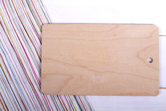 Cutting board over striped towel on wooden kitchen table. Royalty Free Stock Images