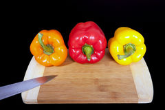 Cutting board with paprika and knife. Three home peppers on black background. Stock Image