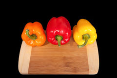 Cutting board with paprika. Three home peppers on black background. Royalty Free Stock Photos