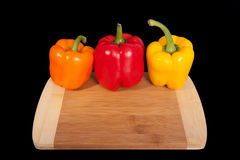 Cutting board with paprika. Three home peppers on black background. Stock Photos