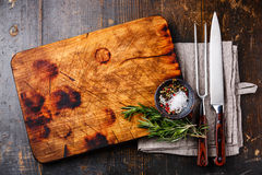 Cutting board, pepper and rosemary with fork and knife Royalty Free Stock Images