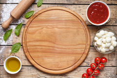 Cutting board with pizza ingridients: mozzarella, tomatoes sauce, basil, olive oil, cheese, spices. Italian pizza royalty free stock images