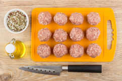 Cutting board with raw meatballs, vegetable oil, spices and knif Royalty Free Stock Image