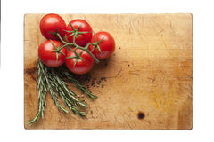 Cutting board with rosemary and tomatoes. Wooden cutting board with rosemary and tomatoes, empty space Royalty Free Stock Photography