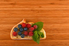 Cutting board with sandwich of blueberries and raspberries on br. Better than caviar - cutting board with sandwich of mellow blueberries, raspberries and mint Royalty Free Stock Images