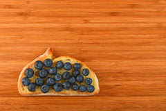 Cutting board with sandwich of blueberries on slice of bread Stock Image