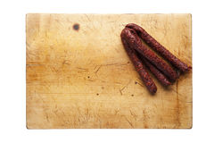 Cutting board with sausage. Wooden cutting board with sausage, empty space Royalty Free Stock Image
