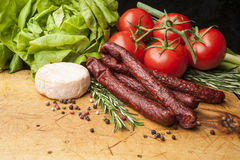 Cutting board with sausages and various vegetables. Wooden cutting board with sausages and vegetables Stock Images
