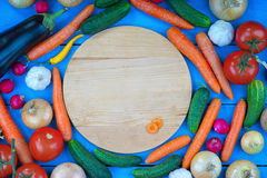 Cutting board with sliced carrot among fresh vegetables Stock Images