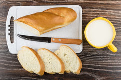 Cutting board, slices of bread, knife and cup with milk Royalty Free Stock Image