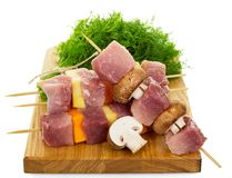 Cutting board, slices of raw pork, vegetables and mushrooms on w. Ooden skewers, dill isolated on white background Stock Photo