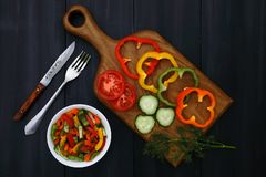 A cutting board with slices of tomatoes, cucumbers and peppers, a branch of dill, a fork and a knife, a plate of vegetable salad royalty free stock photo