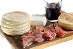 Cutting board with small round flat bread, ham, cheese and glass of red wine Royalty Free Stock Photos