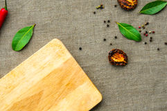 Cutting board and spices on linen fabic as a blank template food  background, top flat view Royalty Free Stock Image