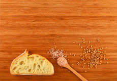 Cutting board with spoon of Himalayan  salt, wheat grains and br Royalty Free Stock Photo