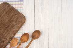 Cutting board and a spoon on a kitchen napkin on old wooden tabl Stock Images