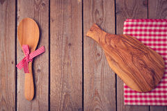 Cutting board and spoon on wooden table. View from above Royalty Free Stock Image