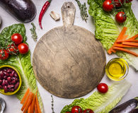 Cutting board with a spread out around vegetables, beans, tomatoes, lettuce place for text, frame  wooden rustic background top Stock Photos