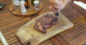 Cutting Board Steak. Grilled ribeye steak on a cutting board on wooden table stock video
