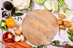 Cutting board surrounded by fresh raw vegetables. Round empty cutting board surrounded by fresh raw vegetables as carrots, potatoes, onion, pepper, cauliflower Stock Photos