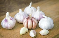 Garlic on a cutting Board on the table. On a cutting Board on the table are the bulb and the teeth of garlic Royalty Free Stock Photos