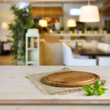 Cutting board on table over blurred restaurant interior background.  Royalty Free Stock Images