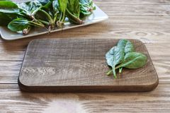 cutting board on a table with spinach leaves, a plate of spinach in the background. Meal preparation concept royalty free stock photo