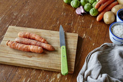 Cutting board with three raw carrots Stock Photos