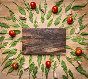Cutting board with tomatoes and herbs around place for text, frame wooden rustic background top view Royalty Free Stock Photo