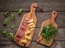 Cutting board with traditional Italian salami and cheese with herbs on rustic background. Royalty Free Stock Image
