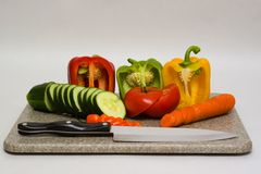 Cutting board with vegetables. A cutting board with cut vegetables and a chefs knife Royalty Free Stock Photography