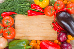 Cutting board with vegetables. Blank wooden cutting board with colorful vegetables Royalty Free Stock Photography