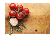 Cutting board with vegetables and cheese. Wooden cutting board with rosemary and tomatoes, cheese. Empty space for your product Stock Photography