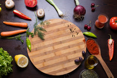 Cutting board and vegetables and spices around. Photo from above on the table Stock Images