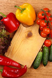 Cutting board and vegetables Stock Images