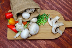 A cutting board with vegetables. On wooden background stock images