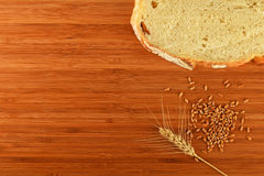 Cutting board with wheat ear, grains and slice of bread Royalty Free Stock Photo