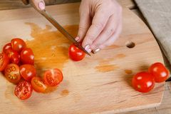 On a cutting board, a woman knives the regime of cherry tomatoes into slices for vegetable salad. Front view, close-up Royalty Free Stock Photo