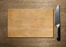 Cutting board on wood table. Display of cutting board with knife Stock Photography