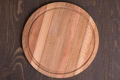 Cutting board on wooden background Royalty Free Stock Photos