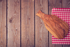 Cutting board on wooden table. View from above Stock Photo